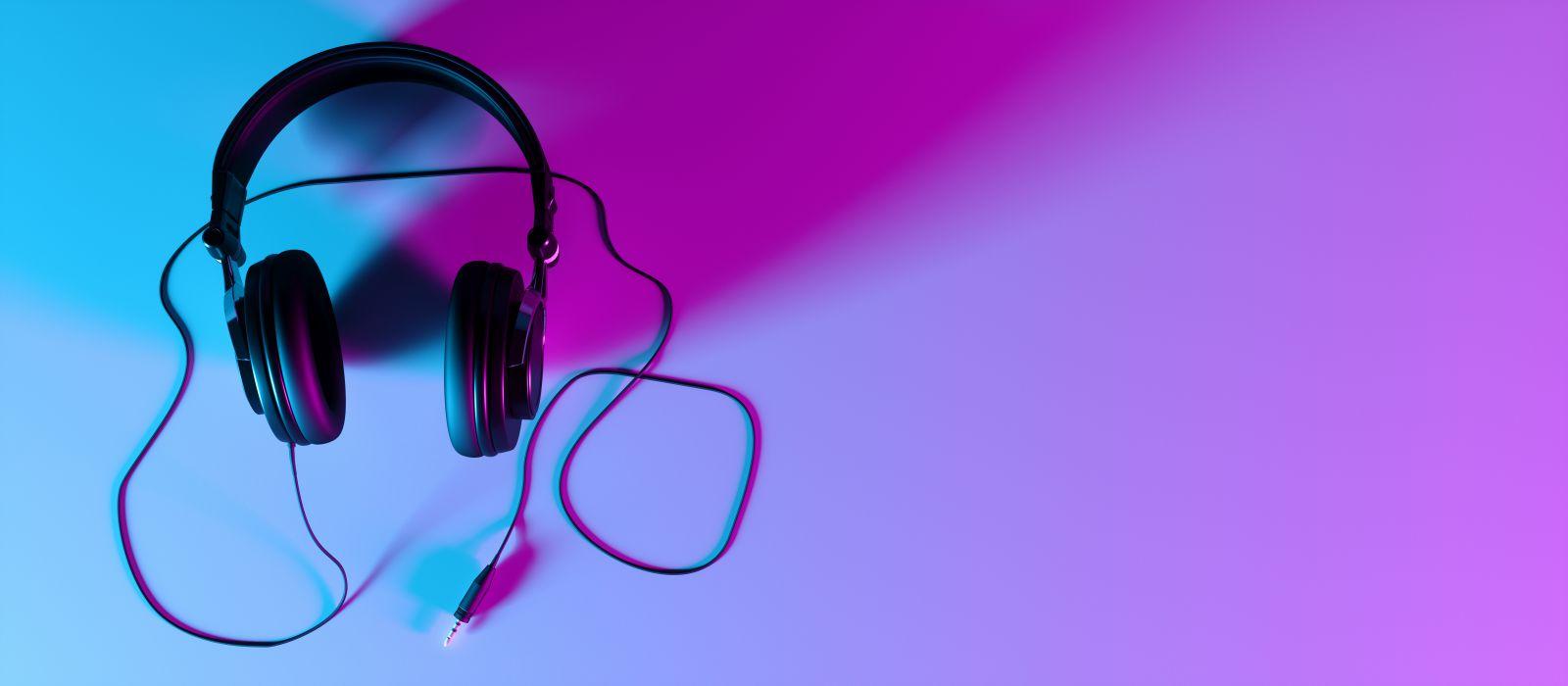 Black wired headphones on a magenta lit white desk